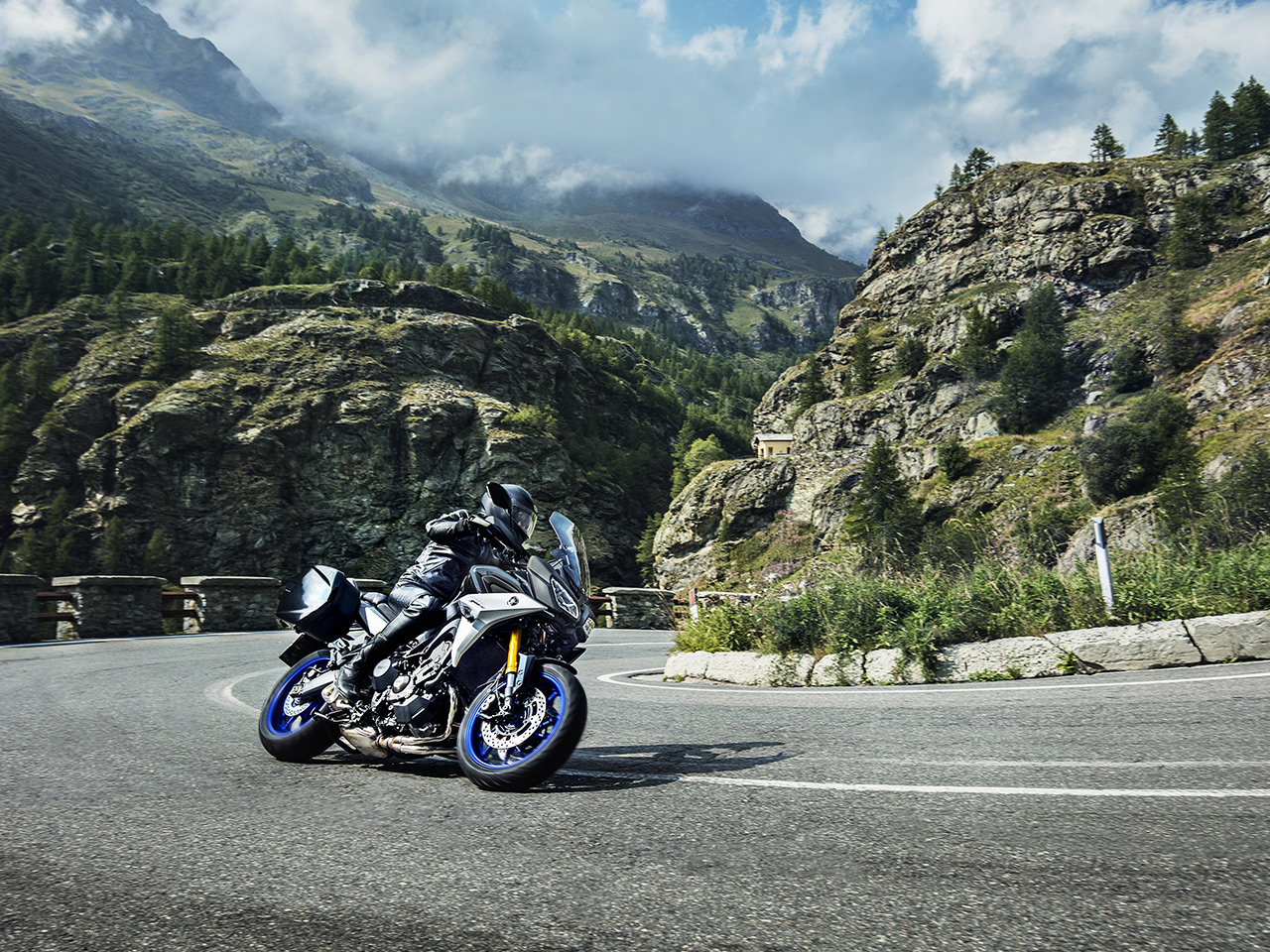 Yamaha Tracer 900 GT motorcycle riding on the hill road