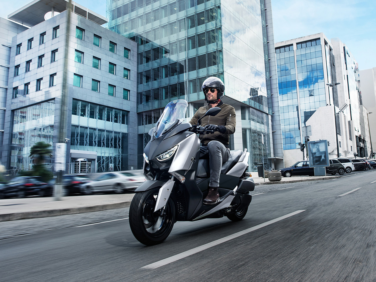 Yamaha XMAX 300 scooter in Matt Silver colour riding down city street