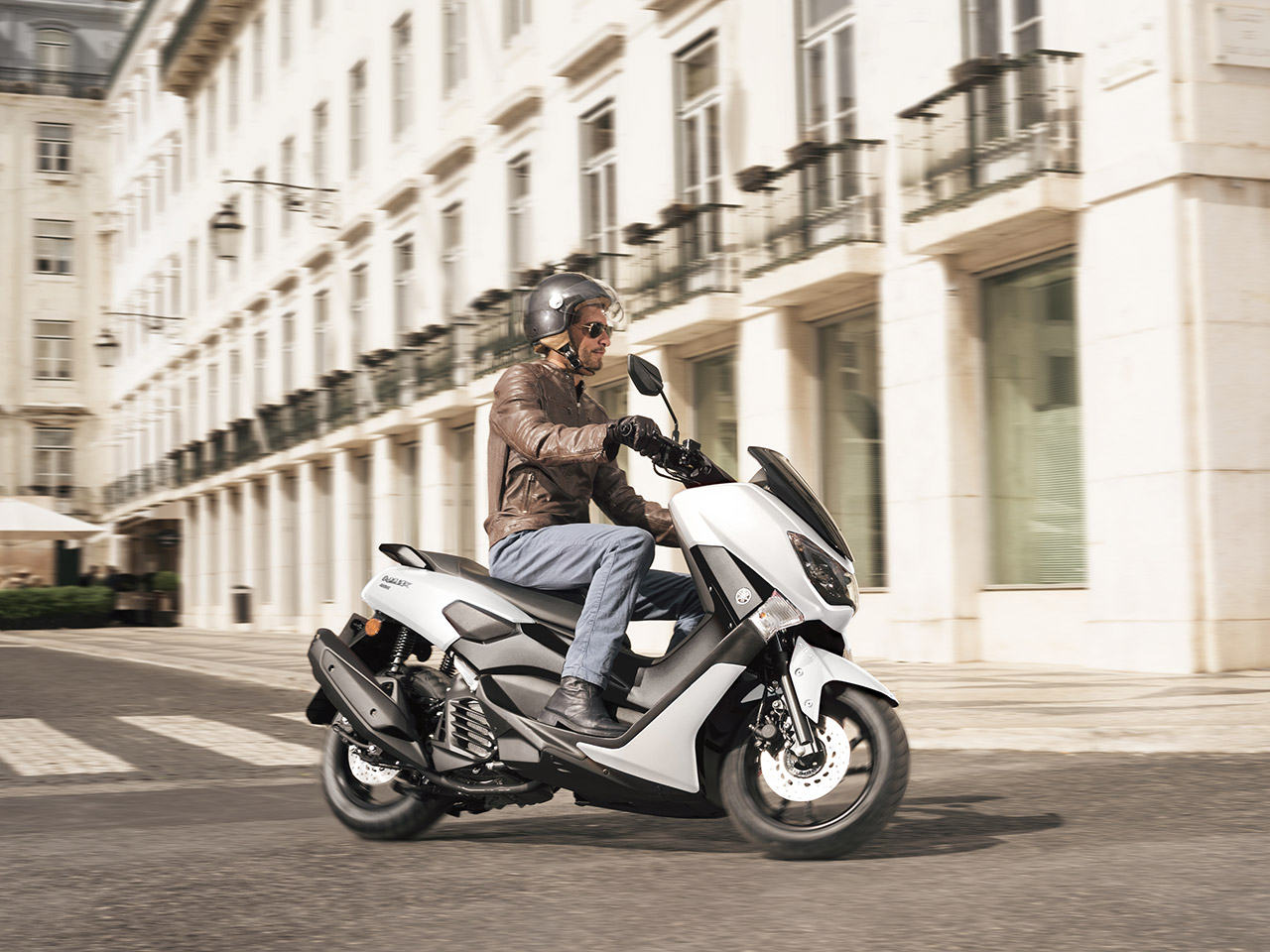 Yamaha NMAX 155 scooter in Milky white riding down city street